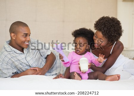 Happy parents and baby girl sitting on bed together at home in the bedroom - stock photo