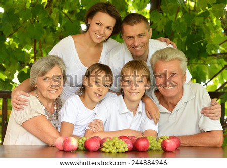 Happy parents and children at a table eating fruits in summer