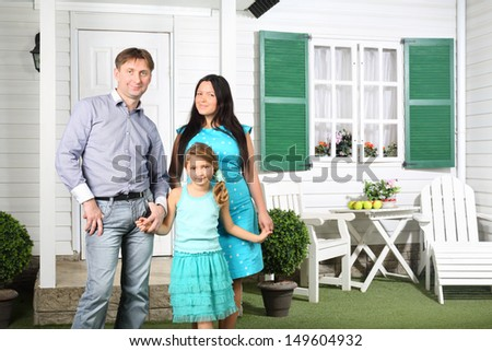 Happy parents and cute little daughter stand next to new house with green shutters. - stock photo