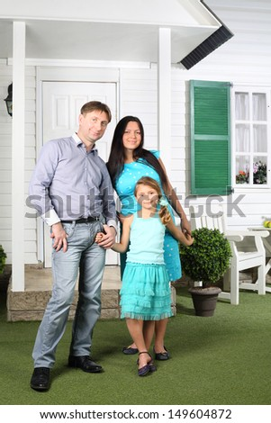 Happy parents and daughter stand next to house with green shutters.