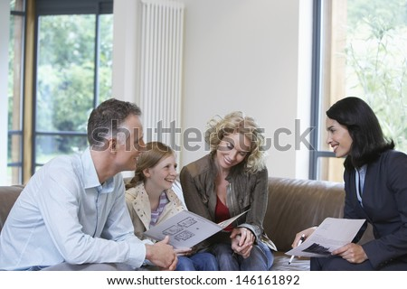 Happy parents and daughter with female estate agent discussing new property - stock photo