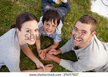 Happy parents and kid lying on garden - stock photo