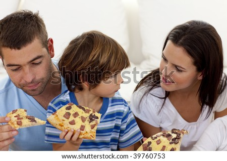 Happy parents and son eating pizza in living-room all together