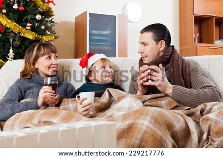 Happy parents and teenage son with cups of tea warming near warm calorifer in Christmas time - stock photo