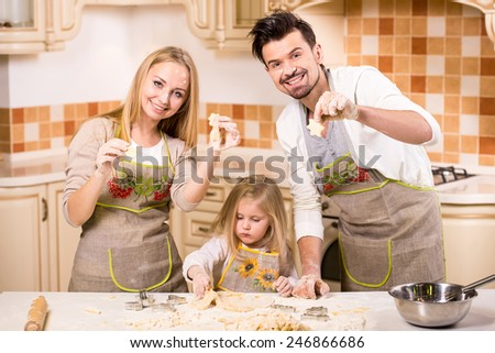 Happy parents and their young daughter are cooking, baking cakes in home kitchen. - stock photo