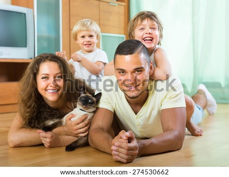 Happy parents and two daughters lying on the floor at home with Siamese. Focus on man  - stock photo