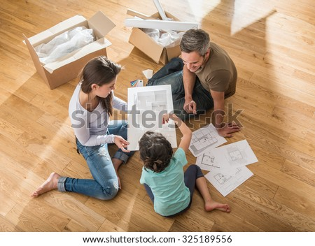Happy parents are sitting barefoot on the floor of their new house They are looking at the house model with their daughter They are surrounded by open cardboard boxes and palette for the paint - stock photo