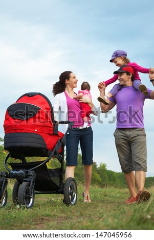happy parents are walking with their little daughters  in park - stock photo