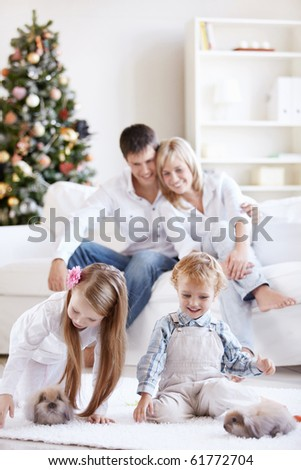 Happy parents are watching as children play with the rabbits - stock photo