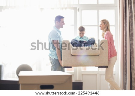Happy parents carrying son on armchair in new house - stock photo