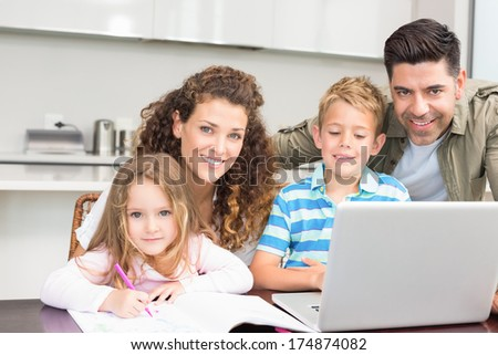 Happy parents colouring and using laptop with their children at home in kitchen