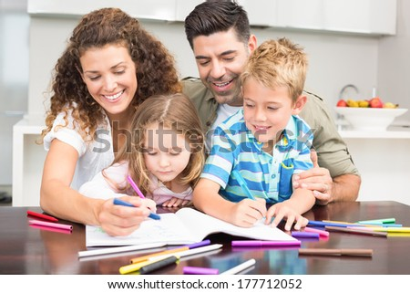 Happy parents colouring with their children at the table at home in kitchen - stock photo