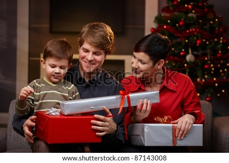 Happy parents giving christmas gifts to their son, smiling. ? - stock photo