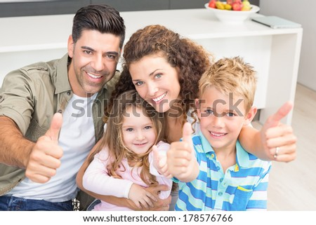 Happy parents giving thumbs up with their young children at home in kitchen - stock photo