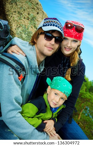 Happy parents hiking with their little son.