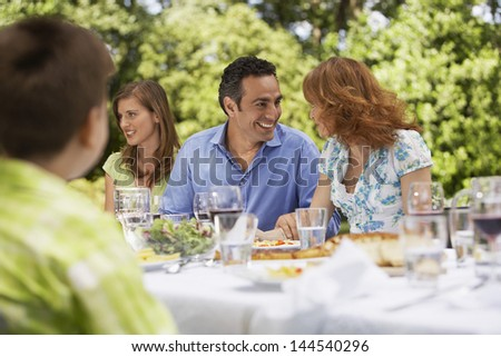 Happy parents looking at each other while having lunch with family in backyard - stock photo