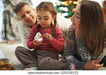 Happy parents looking at their cute daughter with cupcake - stock photo