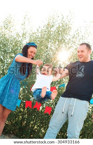 happy parents shake their baby in her arms outdoor. family have fun - stock photo