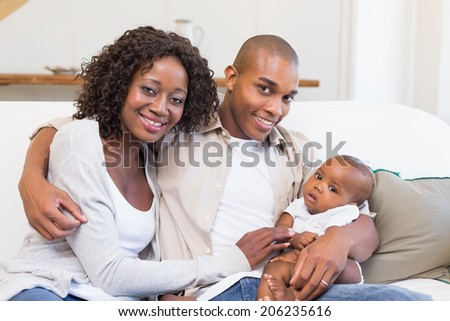 Happy parents spending time with baby on the couch at home in the living room - stock photo
