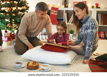 Happy parents teaching their cute daughter how to write - stock photo