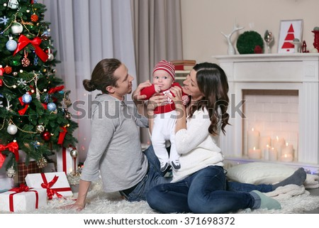 Happy parents with baby near Christmas tree on the floor in the decorated room - stock photo