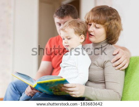Happy parents with child looks the book in home interior