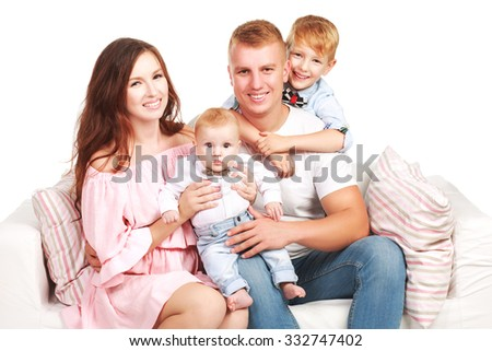 Happy parents with children on the couch with pillows isolated