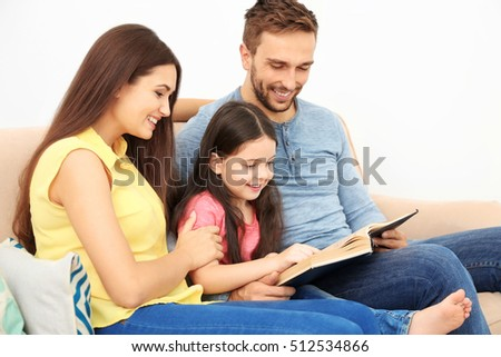 Happy parents with daughter reading book on couch