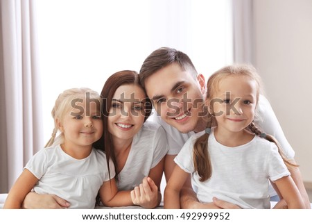 Happy parents with daughters on couch