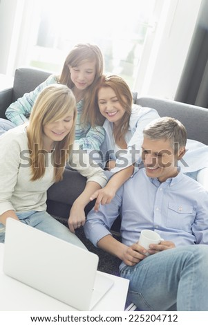 Happy parents with daughters using laptop in living room - stock photo