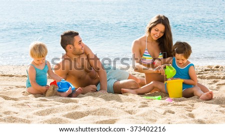Happy parents with kids playing with sand at beach - stock photo