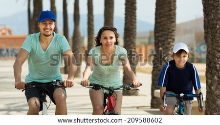 Happy parents with son riding bicycles and smiling - stock photo