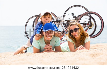 Happy parents with teenager having rest after cycling on the beach - stock photo