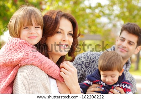 Happy parents with their children in the park. Shallow focus. - stock photo