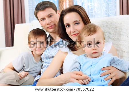 Happy parents with their two son at home. - stock photo