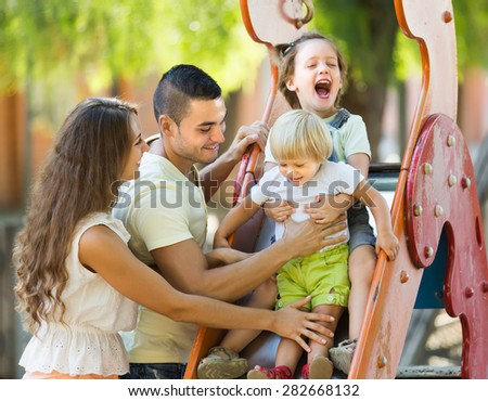 Happy parents with two daughters playing at children's slide. Focus on man