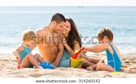 Happy parents with two kids in a sea background - stock photo