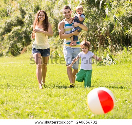 Happy parents with two kids playing with a ball and a walking outdoors - stock photo