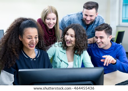 Happy participants of IT lessons are looking at the computer screen
