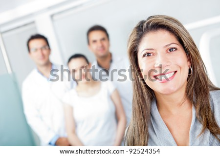 Happy patient at the hospital with a group of doctors - stock photo