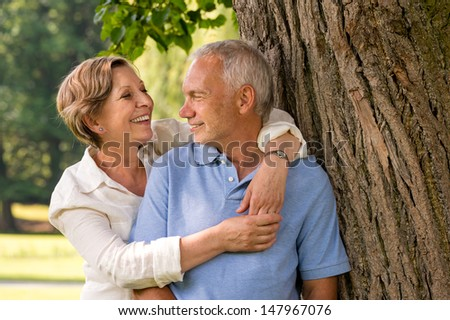 Happy pensioner couple cuddling outdoors leaning against tree