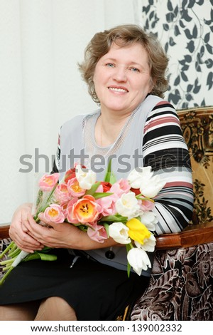 happy pensioner sitting in a chair with a bouquet of tulips - stock photo