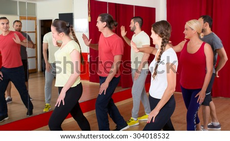 Happy people dancing in a gym indoors - stock photo