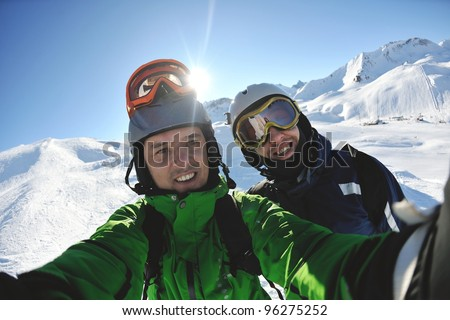 happy people group have fun on ski snow at winter season on mountain with blue sky and fresh air