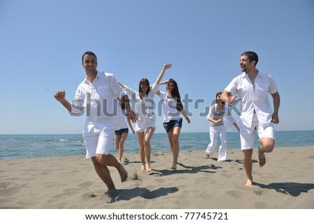happy people group have fun  run and jump  on beach beautiful sand  beach