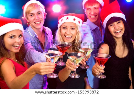Happy people in santa hat clinking by glases with you - stock photo