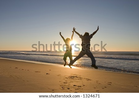 Happy people jumping around at sunrise - stock photo