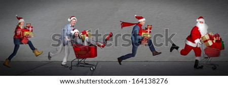 Happy people running with xmas gifts. Christmas sale. - stock photo