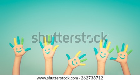 Happy people with smiley on hands against blue summer sky background - stock photo