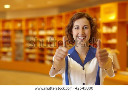 Happy pharmacist holding both thumbs up in pharmacy - stock photo
